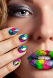 Girl with beautiful multicolor Minx nails and make-up. Half face of attractive girl with beautiful multicolor holographic Minx nails and bright colorful make-up royalty free stock photos