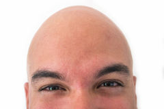 Half face of bald man in white background. Closeup of the eyes. Excited mood Royalty Free Stock Photos
