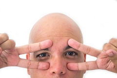 Half face of bald man in white background. Closeup of the eyes. Fingers on the eyes Stock Image