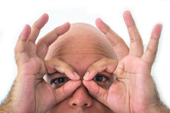Half face of bald man in white background. Closeup of the eyes. Hands simulating a mask Stock Images