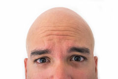 Half face of bald man in white background. Closeup of the eyes. Worry mood Stock Photos