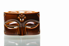 Half face Balinese pottery. This aroma therapy's pot made look like human face. One of my arts collection, place against very bright background on the glass desk Stock Photos