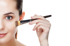Half face of Beauty Girl with Makeup Brushes. Natural Makeup for Stock Photo