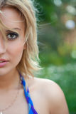 Half face of blond woman walking in summer forest stock photography
