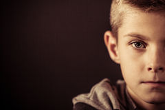 Half Face of a Boy Against Brown with Copy Space. Close up Serious Half Face of a Boy Staring Straight at the Camera Against Dark Brown Background with Copy Royalty Free Stock Photos