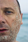 Half face covered with sand. Half face of a handsome man covered with sand stock photos
