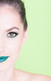 Half face of lady wearing professional make-up. Half face of lady wearing professional green trendy make-up isolated on green background Royalty Free Stock Photos
