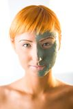 Half face masked. Young red-haired woman with green mask on half face. Looking at camera, front view. Closeup on face Royalty Free Stock Images