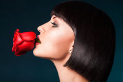 Half face portrait of pretty woman with red rose Stock Photo