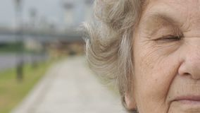 Half face of serious elderly woman outdoors stock footage