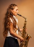 Half-face view of girl playing alto saxophone Royalty Free Stock Image