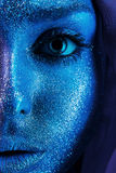 Half face of woman in blue bodyart Stock Photography