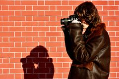 Profile of a young photogropher shooting wih camera against brick wall royalty free stock images
