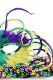 Half of a Feathered mardi gras mask on beads. Feathered Mardi Gras mask laying on colorful beads Royalty Free Stock Photo