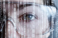 A half of female face in virtual reality glasses with binary codes stock image