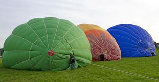 Half-filled hotair-balloons lying side-by-side Royalty Free Stock Photo
