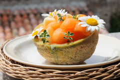Half filled melon decorated in the sunlight. Half filled melon decorated with daisy in the sunlight stock images