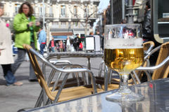 Half-finished glass of beer stands on table in street cafe Stock Photography