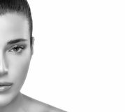 Half Flawless Face of Young Pretty Woman in Monochrome. Closeup Half Flawless Face of Young Pretty Woman in Monochrome at the Left Frame, Looking at the Camera Royalty Free Stock Image