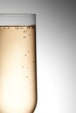 Half flute glass of champagne with bubbles Stock Photography