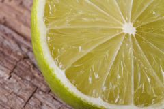 Half of fresh juicy lime on background wooden table Royalty Free Stock Images