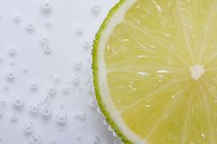 Half fresh lime in water with bubbles Royalty Free Stock Image
