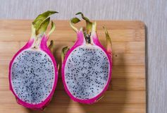 Half of fresh pitaya or dragon fruit lie on the table.  Royalty Free Stock Images