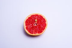 Half a fresh red grapefruit on white background. Half a fresh red grapefruit on a white background Royalty Free Stock Image