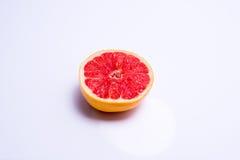 Half a fresh red grapefruit on white background. Half a fresh red grapefruit on a white background Royalty Free Stock Photos