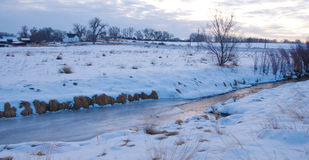 Half Frozen Creek in Snowy Scene Stock Photos