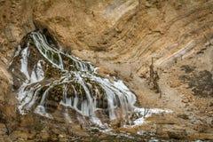 A half frozen waterfall beside Zanskar river royalty free stock photography