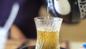 Half full glass of Turkish tea. Drinking traditional Turkish Tea. Turkish tea in traditional glass cup stock video footage