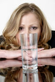 Half full or half empty. Woman staring at a glass of water wondering if its half full or half empty, concept of conception royalty free stock image