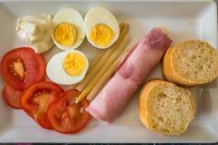Half gekookte eieren, gesneden tomaten, brood en ham stock afbeelding