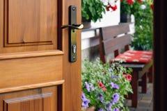Half geopende deur in het mooie de zomerterras en de bloeiende tuin royalty-vrije stock foto's
