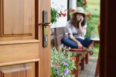 Half geopende deur in het mooie de zomerterras en de bloeiende tuin waar de jonge vrouw zit, ontspant en telefoneert royalty-vrije stock foto