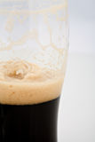 Half gone. A half drained pint of stout beer Royalty Free Stock Photos