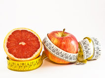 Half grapefruit and apple with tape measure Stock Photography