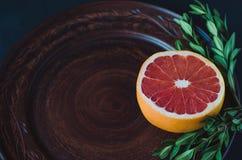 Half a grapefruit on a clay plate stock photos