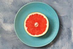A half of a grapefruit closeup on grey background.