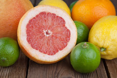 Half grapefruit with other fruits on wood Stock Photos