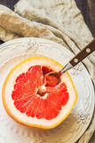 Half a grapefruit on vintage plate with spoon Stock Images