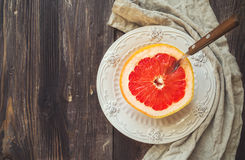 Half a grapefruit on vintage plate with spoon Stock Photo