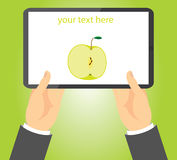 Half green apple on a tablet held in hands Stock Photo