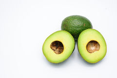 Half of green avocados  on a white. Half of green avocados  on a white background Stock Photo
