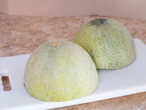 Half of Green japanese melon on a white block in kitchen Royalty Free Stock Photography