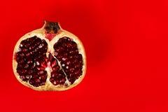 Half grenadine over red background Stock Images
