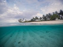 Half and half split scross section of clear sea and empty beach royalty free stock image