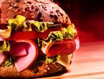 Half of hamburger with ham on wooden board . Royalty Free Stock Photo