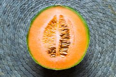 Half of Hami Melon Fruit on Green Straw Mat Background Surface royalty free stock photos